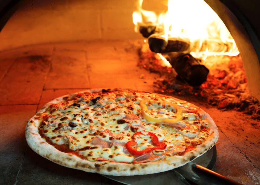 cooking in a wood fired pizza oven